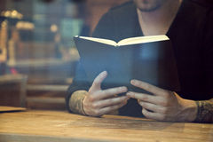 Portrait of handsome white hipster man reading book in cafe. Indoor Royalty Free Stock Photography