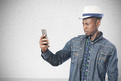 Portrait of a handsome young african man standing with a mobile stock photo