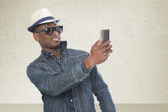 Portrait of a handsome young african man standing with a mobile royalty free stock photos