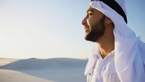 Portrait of handsome young Arabian Sheikh who drinks from cup of. Shooting close-up portrait of attractive and happy Muslim man who enjoys aroma of coffee and Royalty Free Stock Photos