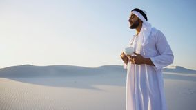 Portrait of handsome young Arabian Sheikh who drinks from cup of. Shooting close-up portrait of attractive and happy Muslim man who enjoys aroma of coffee and Stock Image