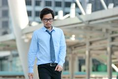 Portrait of handsome young Asian businessman walking to forward on blurred urban building city background. stock photo