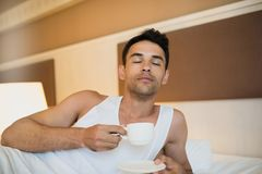 Portrait of handsome young awake man drinking cup of coffee with. Closed eyes in the white bed. Bedroom background Stock Photo