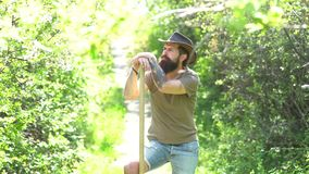 Portrait of handsome young bearded man on spring background. Retro advertising of alcoholic beverages. Ecology concept. stock video footage
