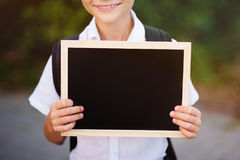 Portrait of handsome young boy . Education concept. Outdoors. The schoolboy holds an empty chalkboard for writing Stock Images