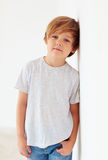 Portrait of handsome young boy, kid posing near the white wall stock image