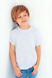 Portrait of handsome young boy, kid posing near the white wall royalty free stock image