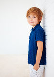 Portrait of handsome young boy, kid posing near the white wall Royalty Free Stock Images