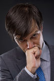 Portrait of handsome young business man thinking. Against a gray background Royalty Free Stock Photography