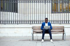 Handsome young business man using his laptop in the street. Portrait of handsome young business man using his laptop in the street Royalty Free Stock Images