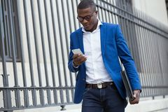 Handsome young business man using his mobile phone in the street Stock Photos