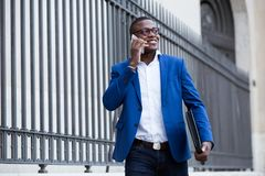Handsome young business man using his mobile phone in the street Stock Images