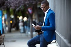 Handsome young business man using his mobile phone in the street Stock Photography