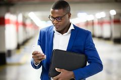 Handsome young business man using his mobile phone in the street Royalty Free Stock Image