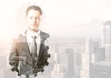 Collaboration and future concept. Portrait of handsome young businessman on abstract city background with cogwheel silhouette and copy space. Collaboration and Stock Photography