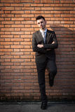 Portrait of a handsome young businessman against a brick wall Stock Photography