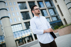 Portrait of handsome young businessman carrying laptop. Outdoors Stock Image