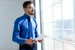 Handsome young businessman holding papers and looking sideways in the office. Stock Photos