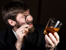 Portrait of handsome young businessman looking at brandy through magnifying glass.  Stock Photos