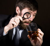 Portrait of handsome young businessman looking at brandy through magnifying glass.  Royalty Free Stock Images
