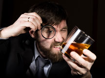 Portrait of handsome young businessman looking at brandy through magnifying glass.  Royalty Free Stock Photography