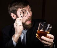 Portrait of handsome young businessman looking at brandy through magnifying glass.  Stock Photography