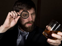 Portrait of handsome young businessman looking at brandy through magnifying glass.  Royalty Free Stock Photos