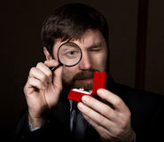 Portrait of handsome young businessman looking at precious ring through magnifying glass.  Royalty Free Stock Photos