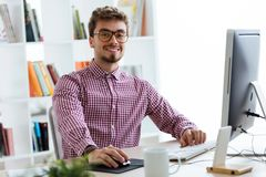 Handsome young businessman using his laptop in the office. Royalty Free Stock Image