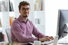 Handsome young businessman using his laptop in the office. Stock Photo