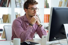 Handsome young businessman using his laptop in the office. Royalty Free Stock Images