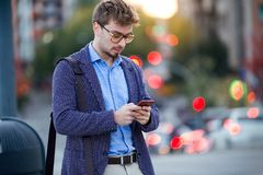 Handsome young businessman using his mobile phone in the street. Stock Photography