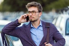 Handsome young businessman using his mobile phone in the street. Royalty Free Stock Images