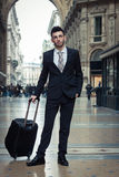 Portrait of a handsome young businessman with wheeled suitcase Stock Images