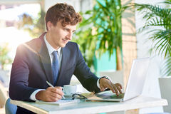 Handsome Businessman Working at Desk. Portrait of handsome young businessman working at desk using laptop and smiling in sunlight Royalty Free Stock Image