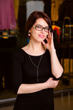 Portrait of a handsome young businesswoman in a shopping center. Portrait joyful Office worker, correct glasses.  behind  Showcases with clothing store stock photo