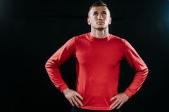 Portrait of handsome young Caucasian athlete relaxing after hard workout at dark background, standing and holding hands on his wai. Caucasian sportsman wearing Stock Photo