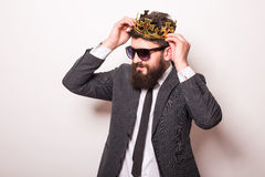 Portrait handsome young cheerful man in suit with crown looking at camera Stock Images