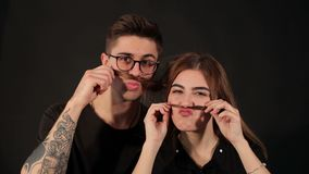 Portrait of young couple making mustache from hair stock video