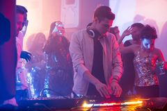 Young DJ Playing in Nightclub. Portrait of handsome young DJ standing at mixer making music during night party in club, scene lit by stage lights with beautiful Royalty Free Stock Images