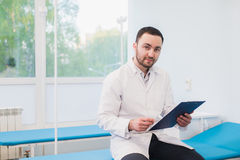 Portrait of handsome young doctor in office Royalty Free Stock Images
