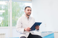 Portrait of handsome young doctor in office Stock Photo