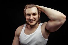 Portrait of a handsome young fair-haired man showing and his big biceps royalty free stock photo
