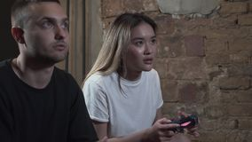 Portrait handsome young guy with his girlfrend playing video games with in modern loft club. Video game and leisure. Concept stock video