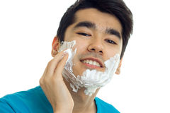 Portrait of a handsome young guy who smiles at the camera and hand shaving foam on your face Stock Image
