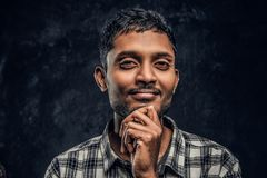 Portrait of a handsome young Indian guy wearing a checkered shirt holding hand on chin and looking at a camera with a royalty free stock photo