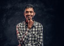 Portrait of a handsome young Indian guy wearing a checkered shirt holding hand on chin and looking at a camera with a stock images
