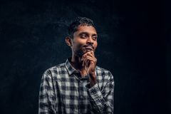 Handsome young Indian guy wearing a checkered shirt holding hand on chin and looking sideways with a pensive look stock photography