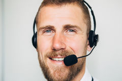 Portrait of handsome young male operator in headset looking at camera and smiling while standing against white royalty free stock photos