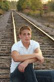 Portrait of Handsome Young Man. Casual portrait of young man sitting on railroad tracks Royalty Free Stock Image